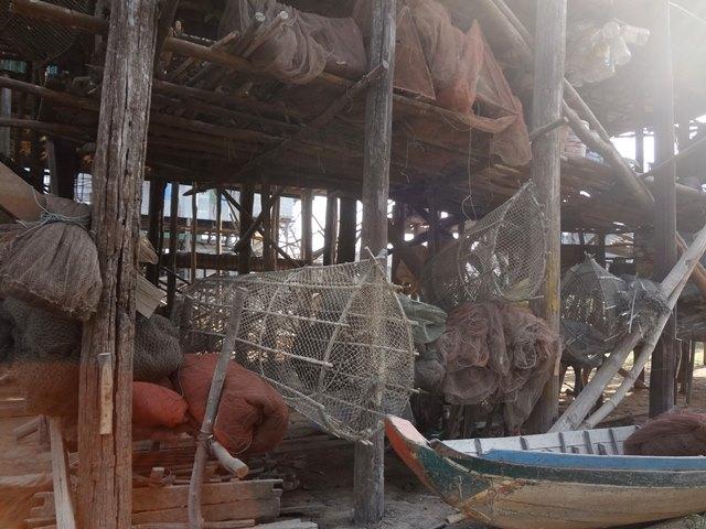 高床式の住居の下に並ぶ漁業の道具